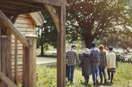 Friends walking outside lakeside cabin Stock Photos