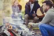 Man frying fish in grill basket over campfire near friends Stock Photos