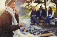 Smiling woman eating roasted marshmallows at campfire Stock Photos