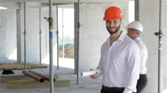 Male builder holds set of plans of building under construction Stock Footage