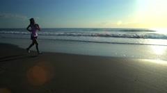 Young slim Asian American sportswoman enjoying jogging on the beach on Summer Stock Footage