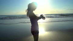 Young slim Asian Chinese woman wearing sport watch on the ocean beach at sunrise Stock Footage
