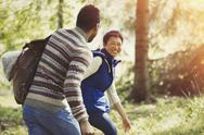Laughing couple hiking with backpack in woods Stock Photos