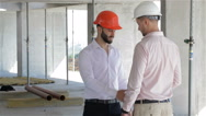 Architector and builder shake hands at the building under construction Stock Footage