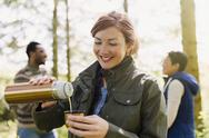 Smiling woman pouring coffee from insulated drink container in woods Stock Photos