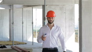 Builder walking with set of plans under his arm Stock Footage