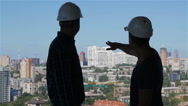 Builder points his hand at the complex of high buildings Stock Footage