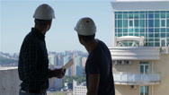Builder points at the penthouse near the building under construction Stock Footage