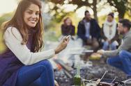 Portrait smiling woman texting and drinking beer at campsite Stock Photos
