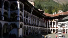 Tourists in courtyard of beautiful male friary Rila Monastery Bulgarian church Stock Footage