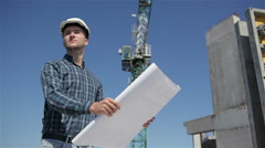 Builder stands with set of plan at the bulding under construction Stock Footage