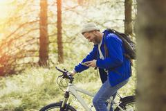 Man mountain biking texting with cell phone in woods Stock Photos