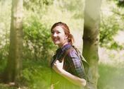 Smiling woman with backpack hiking in sunny woods Stock Photos