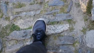 Man legs sneakers walking the paved stones street in old city - POV eyes camera Stock Footage