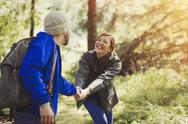 Smiling couple holding hands hiking in woods Stock Photos