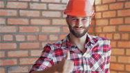 Builder gestures good quality at the building under construction Stock Footage