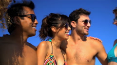 Multi ethnic young males and females wearing swimsuits and sunglasses having fun Stock Footage