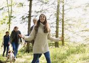 Smiling woman hiking with friends in woods Stock Photos