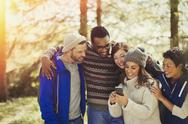 Smiling friends texting with cell phone in woods Stock Photos
