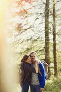 Portrait enthusiastic couple with backpacks hiking in sunny woods Stock Photos