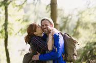 Portrait smiling couple kissing hiking in woods Stock Photos
