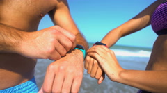 Multi ethnic male and female using sport watch technology to keep fit  Stock Footage