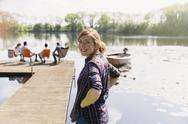 Portrait smiling woman at sunny lakeside dock Stock Photos