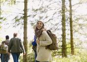 Enthusiastic woman with backpack hiking in sunny woods Stock Photos
