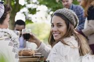 Portrait smiling woman drinking wine at patio lunch with friends Stock Photos