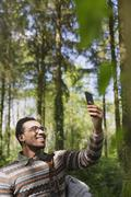 Smiling man taking selfie with camera phone in sunny woods Stock Photos