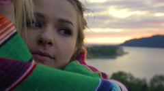 Young Women Get Cozy In Blanket And Hold Each Other At A Scenic Overlook Stock Footage