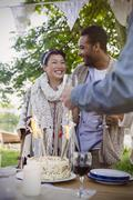 Friends celebrating with birthday cake at patio table Stock Photos
