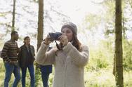 Woman using camera hiking in woods Stock Photos