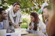 Smiling friends drinking champagne and cutting birthday cake at patio table Stock Photos