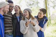 Smiling friends hiking using cell phone in woods Stock Photos