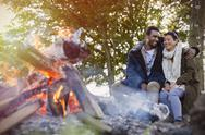 Couple hugging by campfire Stock Photos