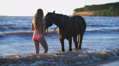 A beautiful blonde young sexy woman standing next to a horse at a lake Stock Footage