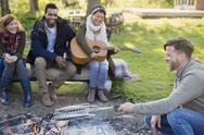 Friends playing guitar and cooking fish in grill basket over campfire Stock Photos