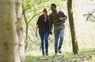 Couple holding hands hiking in woods Stock Photos
