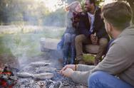 Friends cooking fish in grill basket over campfire Stock Photos