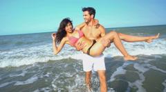 Young loving Caucasian American man carrying his Hispanic woman wearing bikini Stock Footage