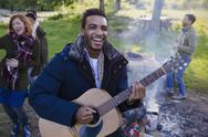Portrait smiling man playing guitar with friends at campsite Stock Photos