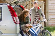 Couple with dog and mountain bike at back of car outside cabin Stock Photos