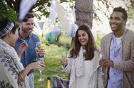 Smiling friends drinking champagne at garden party Stock Photos