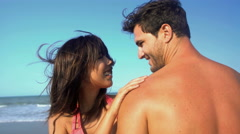 Portrait of young loving multi ethnic couple in swimsuits enjoying their beach Stock Footage