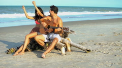 Loving young multi ethnic male and female hanging out and playing the guitar  Stock Footage