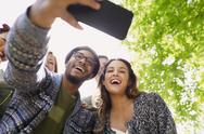 Enthusiastic friends taking selfie with camera phone below tree Stock Photos