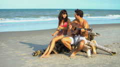 Happy smiling multi ethnic couple hanging out and playing the guitar  Stock Footage