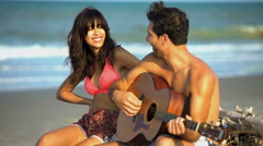 Happy multi ethnic couple in swimwear sitting on driftwood and playing  Stock Footage