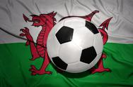 Black and white football ball on the national flag of wales Stock Photos